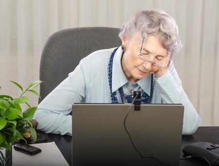 telecommute: Old teacher is falling asleep in front of laptop monitor during lesson online