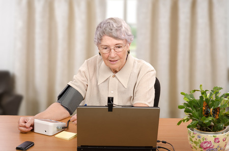 grey haired: Old grey haired woman demonstrates how easy to monitor blood pressure at home then transmit it to telehealth center