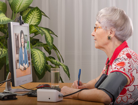 Old grey haired woman is measuring blood pressure while virtual doctor consults her on monitor screen