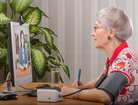 Oude grijze haired vrouw is het meten van de bloeddruk, terwijl virtuele arts raadpleegt haar op beeldscherm Stockfoto