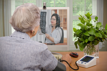 Old retired woman sitting in front of telemedicine physician looks at CT x-ray on the screen 스톡 콘텐츠
