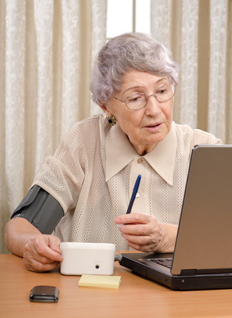 Retired old woman sent her blood pressure information to telemedicine center and waiting answer from physician