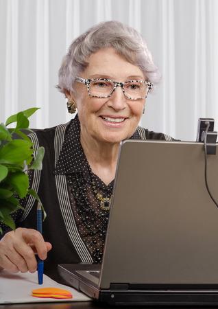 english language: Smiling experienced tutor is teaching English language online Stock Photo