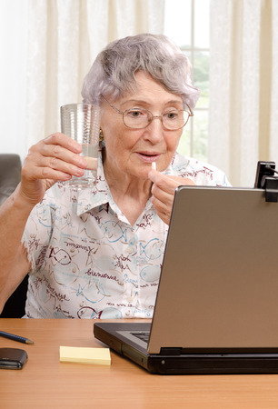 70 75 years: Senior grey haired woman is taking pill during disagreeable conversation on the Internet