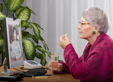 Grey haired patient taking a pill during medical consultation online