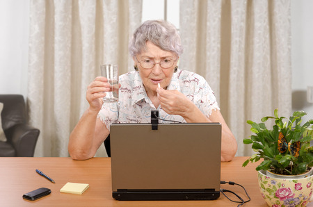 70 75 years: Senior woman is taking pill during reading bad news on the laptop monitor