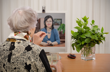 Senior woman taking a pill in front of virtual physician on the monitor screen