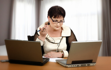 learners: Confident experienced coach is training online with learners by two laptops at the same time Stock Photo