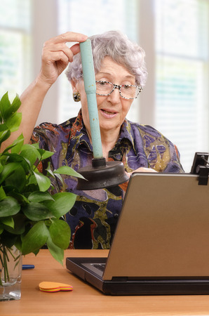 70 75 years: Senior woman with plunger toilet asking help in internet Stock Photo