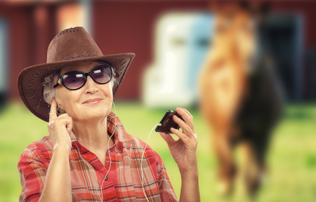70 75 years: Aged cowgirl in brown hat listening country music with smart phone