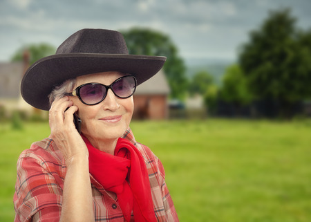 70 75 years: Smiling aged cowgirl in black hat talking on smart phone