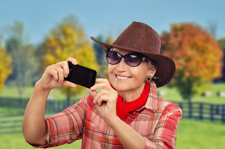 70 75 years: Cheerful aged cowgirl in red neckerchief is making selfie photo with smartphone Stock Photo