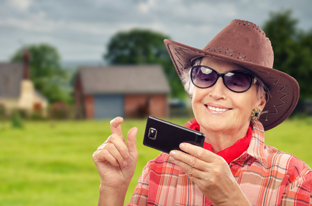 70 75 years: Aged cowgirl in red neckerchief looking photos on smartphone