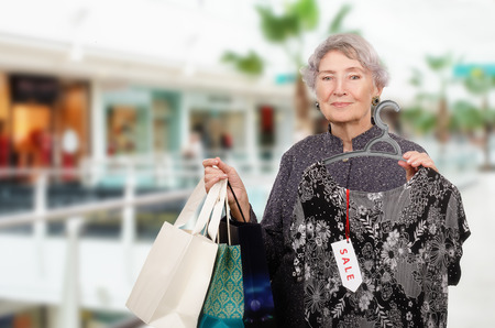 70 75 years: Amazing senior woman staying in shopping mall with three shopping bags in left hand. In right hand, she holds elegant long dress on hangers