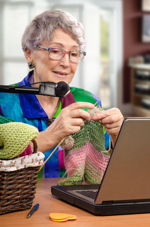 additional training: Vertical portrait of aged woman is knitting in front of laptop. She is training online knitting. Old woman is using additional webcam. It helps learners make out better.
