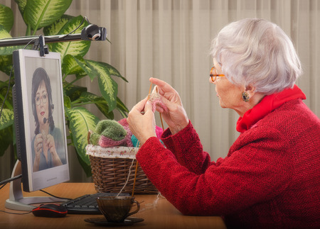 side shot: Well-trained private teacher is explaining to online learner how to knit.  Senior woman is knitting in front of desktop. Two webcams are carefully tracing her work for staring student in monitor. Side shot Stock Photo