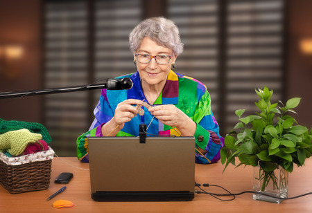 learners: Grey-haired woman is knitting in front of laptop. She is teaching online learners the art of knitting. Experienced teacher is using two webcams to help students in training.
