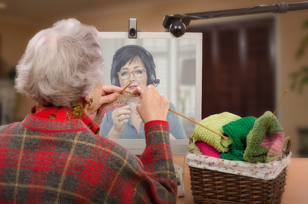 grey haired: Experienced tutor is teaching adult learner the art of knitting via internet. Old grey haired woman is knitting in front of desktop. Two webcams are carefully tracing her work. Student is learning in other end. Shallow depth of field