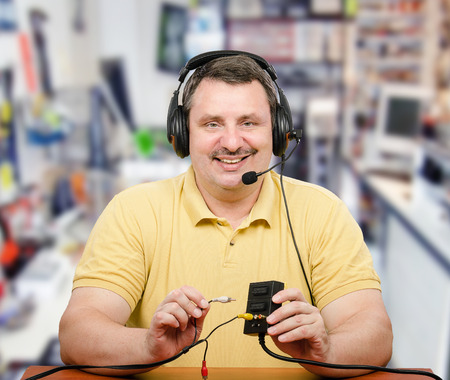 telecommute: Portrait of computer service technician in headset.  Middle-aged man is consulting via internet. Stock Photo