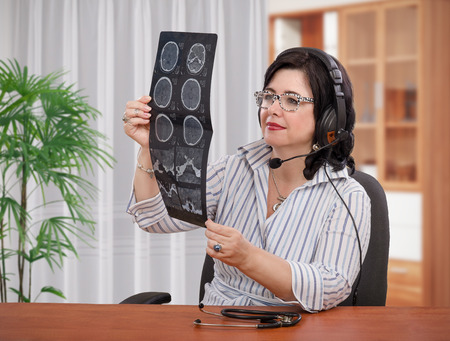 Telehealth doctor in headset is looking at computer tomography brain scan carefully Stock Photo - 42214069