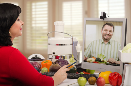 gente saludable: Aut�nomos dietista est� trabajando en el Internet con su cliente. Ella ayuda al hombre de mediana edad con la planificaci�n del men�. Foto de archivo