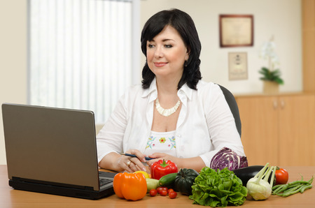 Dietitian is working online in her office. She is sitting in front of laptop surrounded a variety of fresh vegetables