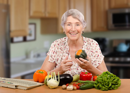 Smiling senior woman is sitting at the table with fresh vegetables. She is online client of dietitian. Nutritionist helps her with menu planning