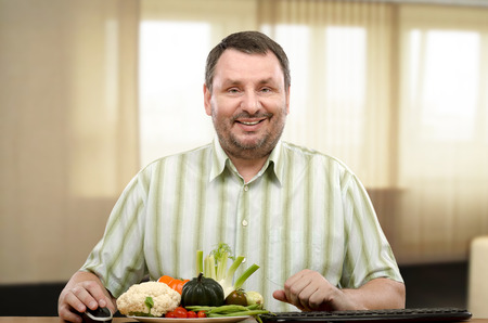 telecommute: Man is sitting at the table with fresh vegetables. He is online learner of dietitian. The man is interesting to know what foods to eat in order to weight loss. Stock Photo