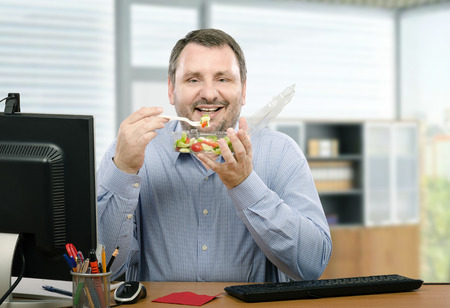 lunchtime: Middle-aged bearded man sitting at desk is healthy eating fan. He orders takeaway vegetable salad every lunchtime. The man wants to lose weight