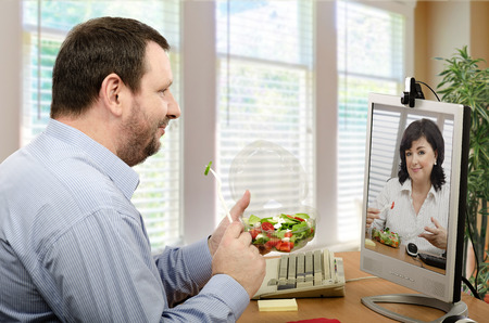 lunch hour: Office workers have ordered takeaway vegetable salad. They are enjoying healthy lunch and pleasant video chat at the same time now Stock Photo