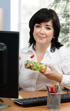 lunch hour: Middle-aged businesswoman eats healthy vegetable salad for every lunch hour in office. Vertical portrait of black haired woman sitting with takeaway transparent container at desk.