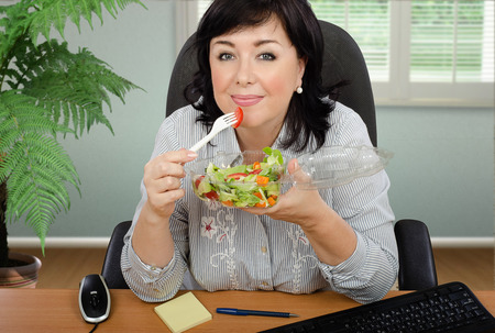 woman eating: Black haired woman eating vegetable salad from transparent plastic container at office desk Stock Photo