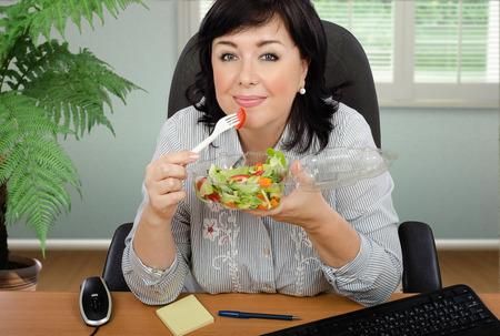 personas comiendo: De pelo negro ensalada mujer comiendo vegetales procedentes de un recipiente de plástico transparente en el escritorio de oficina Foto de archivo