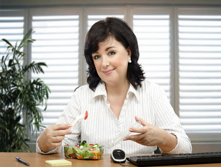lunchtime: Middle-aged businesswoman sitting at desk is healthy eating fan. She orders takeaway vegetable salad every lunchtime Stock Photo