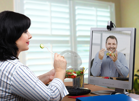 lunch hour: Two healthy eating fans have ordered takeaway vegetable salad for office lunch hour. They are eating and talking by online Stock Photo