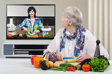 grey haired: Grey haired old woman is looking at wall-mounted TV and cutting zucchini on the table. In the screen, nutrition consultant explains how to make healthy vegetable food