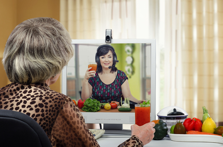 taught: Smiling nutritionist has just taught woman in gray-haired wig how to make a detox drinks at home during online lesson