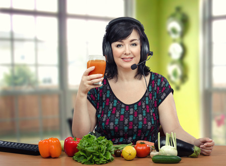 telecommute: Woman in headphones making cleansing detox drinks during online lesson