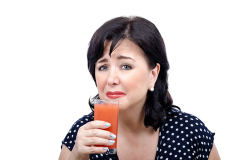 mid adult: Mid adult woman with glass of detox drink can not hold back her tears