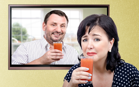 Portrait of mid adult sad woman holding glass of detox drink on the background of smiling nutritionist on the screen of wall-mounted TV