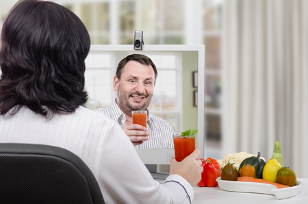 taught: Nutrition coach has just taught black haired woman how to make a detox drinks at home during online lesson Stock Photo