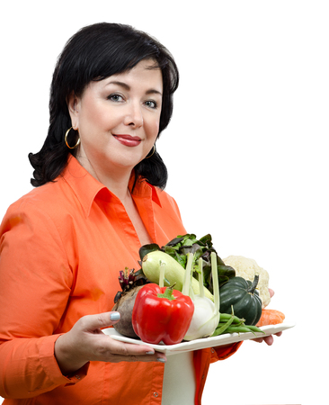 confident woman: Half length portrait of mid adult woman holding a tray of vegetables