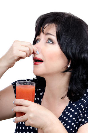 disinclination: Mid adult woman is tired of detox drinks, but she is refusing to give in. She has just held her nose and goes on.