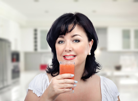 mid adult: Horizontal portrait of mid adult woman holding a glass of detox drink. She is a fan of detox diet