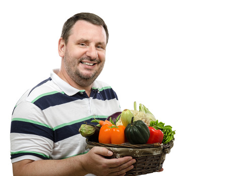 promoting: Cheerful bearded farmer is promoting a basket of fresh vegetables on white background