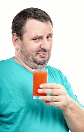 discontented: Middle aged discontented man is holding glass of detox drink on white background