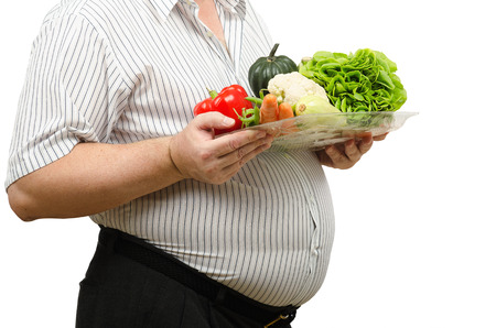 belly pepper: Hands are holding a plastic tray with fresh vegetables on the background of man big belly