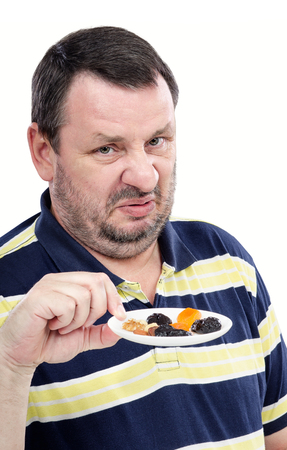 perplexity: Vertical portrait of middle aged bearded man hates a dried fruits