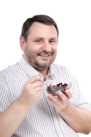 fond: Vertical portrait of cheerful middle aged man is fond of a beet salad