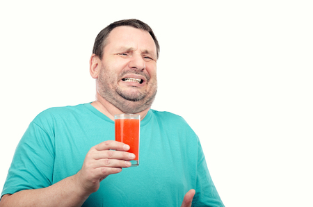 Portrait of middle aged irritated man is holding glass of detox drink on white background Stock Photo